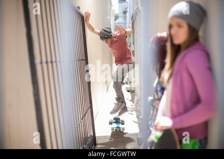 Young man doing a skateboard trick in a passageway - Stock Photo
