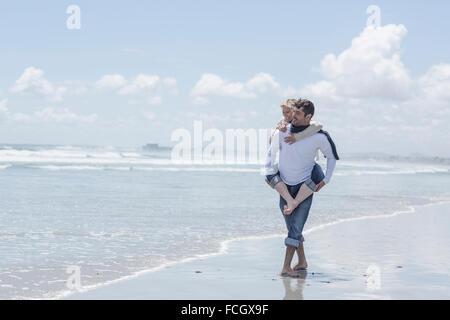 Man giving woman piggyback ride on the beach - Stock Photo