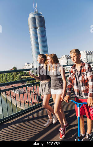 Austria Vienna three teenagers walking on a bridge in front of the Millenium Tower - Stock Photo