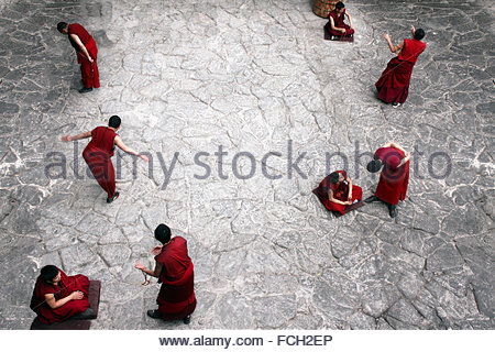 Tibetan buddhist monks debating in Jokhang temple near Lhasa , Tibet - Stock Photo