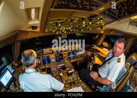 Pilots in the cockpit prepare the Delta Airlines Boeing 777-200LR for the 17 hour flight from Atlanta, Georgia to - Stock Photo