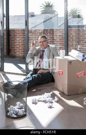 Businessman sitting on the floor in a new office throwing crumpled paper - Stock Photo