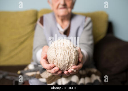 Hands of senior woman holding ball of wool - Stock Photo
