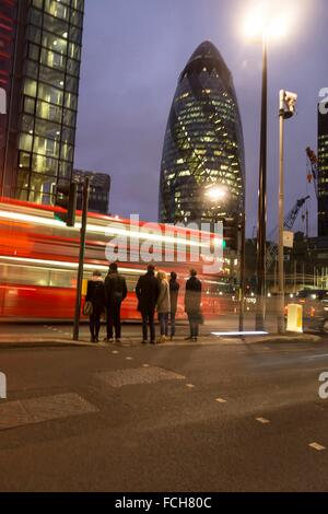 London, UK, The City - Red Double-decker bus zipping in front of pedestrians close to the Gherkin Building at night - Stock Photo