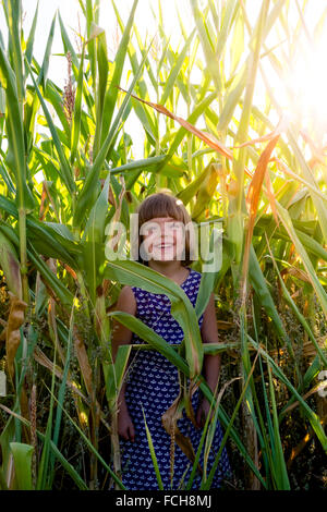 Happy little girl standing in a cornfield - Stock Photo