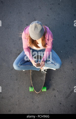 Teenage girl sitting on skateboard looking at cell phone - Stock Photo