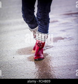 Woman in red boots and blue velvet trousers walks on a wet beach - Stock Photo
