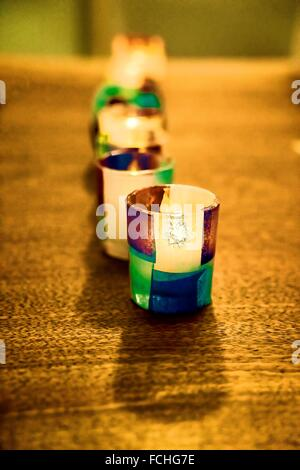 Paper covered glass tea light candle holders, nine in a row, all lit up, decorating a dining room table. - Stock Photo