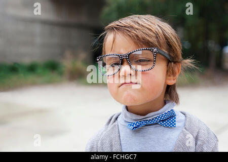 Portrait of little boy wearing oversized spectacles and boy tie making funny face - Stock Photo