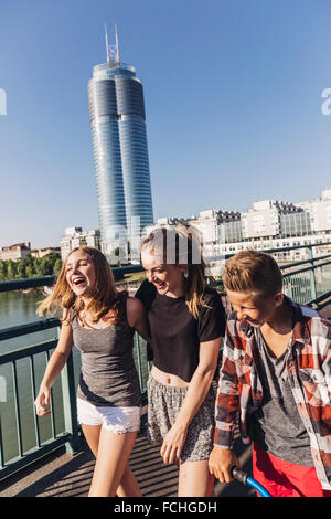 Austria Vienna three happy teenagers walking on a bridge in front of the Millenium Tower - Stock Photo