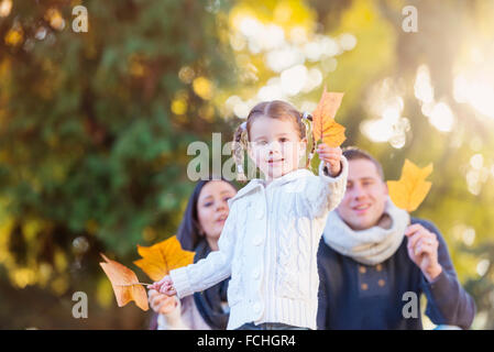 Smiling girl   family holding autumn leaf - Stock Photo