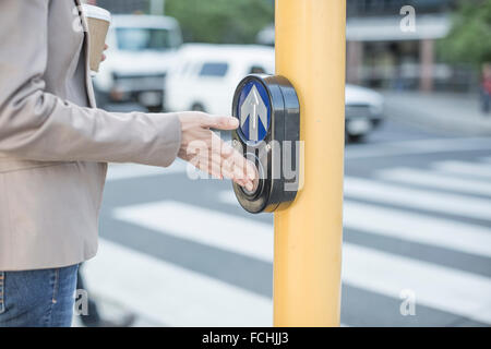 Woman waiting to cross a city street pressing pedestrian crossing button - Stock Photo