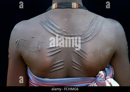 Young woman from the Toposa tribe with decoration scarifications on her back, Omo Valley, Ethiopia, Africa. - Stock Photo