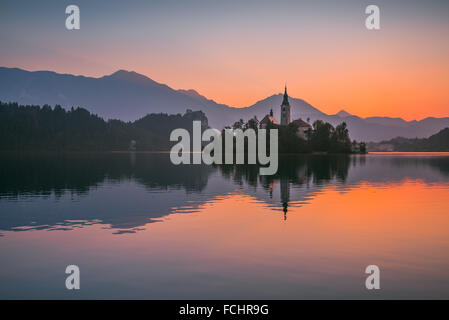 Little Island with Catholic Church in Bled Lake, Slovenia at Sunrise with Castle and Mountains in Background - Stock Photo