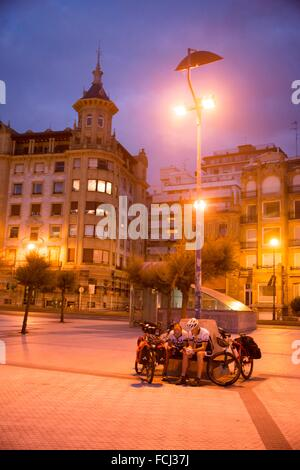 Cycling pilgrims resting under a lamppost in front of San Sebastiás, Basque Country, Spain, Europe - Stock Photo