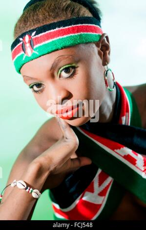 Young Kenyan woman in Kenyan National colors in studio setting - Stock Photo