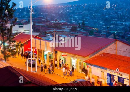 Aerial view of main street - KN 2 Avenue - at dusk, with hillside suburbs beyond, Nyamirambo, Kigali, Rwanda - Stock Photo
