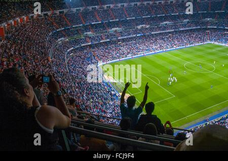 People in Santiago Bernabeu stadium during a football match celebrating a goal. Madrid, Spain. - Stock Photo