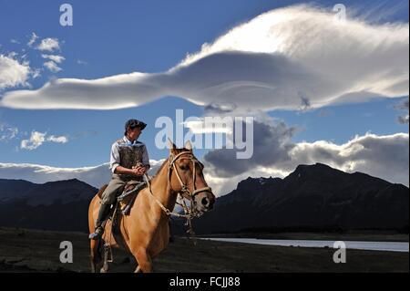 young ´´gaucho´´ on horseback under lenticular clouds, estancia Nibepo Aike on the Argentino lakeshore, around El - Stock Photo