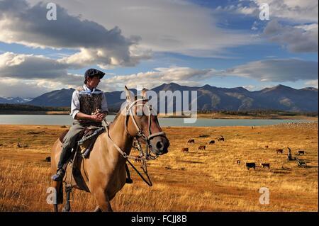 young ´´gaucho´´ on horseback, estancia Nibepo Aike on the Argentino lakeshore, around El Calafate, Patagonia, Argentina, - Stock Photo