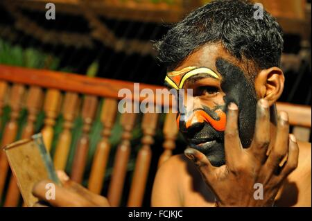 Kathakali performer during making up before a show at the Kumarakom Lake Resort hotel, Kerala state, South India, - Stock Photo