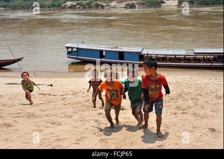 children on the Mekong River bank at Ban Baw, a traditional Lao Loum village between Luang Prabang and Pakbeng, - Stock Photo