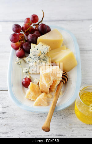 cheese platter with grapes, food close-up - Stock Photo