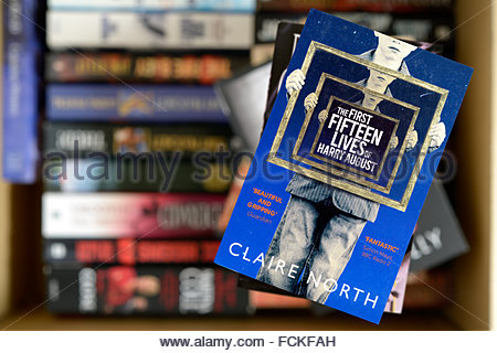 Claire North 2014 novel The First Fifteen Lives of Harry August, stacked used books, England - Stock Photo