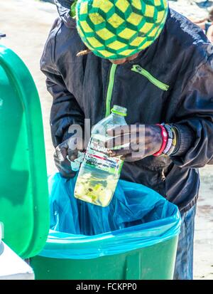 Homeless man scrounges for food in a refuse bin. Cape Town, South Africa - Stock Photo
