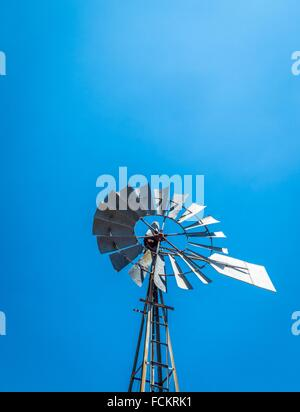 Windmill waterpump reaches for the sky on a farm in the Karoo. South Africa - Stock Photo