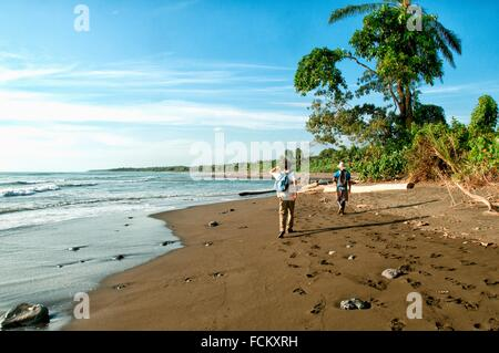 two travellers with backpacks, wild coast of the Pacific Ocean, Corcovado National Park, Costa Rica,. - Stock Photo