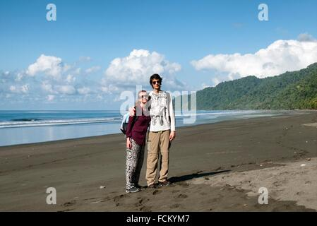 young travellers on empty beach, wild coast of the Pacific Ocean, Corcovado National Park, Costa Rica,. - Stock Photo