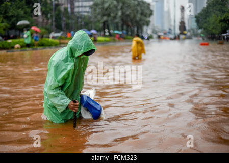 Workers of city planning office trying to find if the street's drainage system is clogged, after a continuous rain left Jakarta flooded.