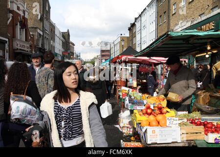 LONDON UK-OCTOBER 12, 2013: Tourists at the market in Portobello road on October 12, 2013 in London. - Stock Photo