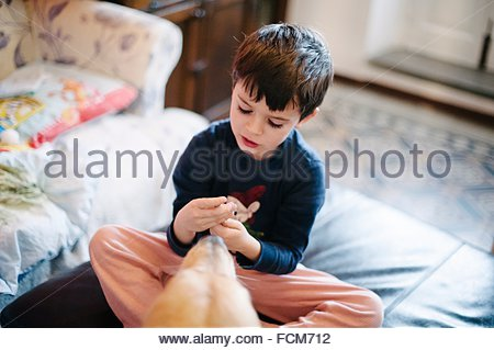 Child plays sitting on poof, dog near - Stock Photo