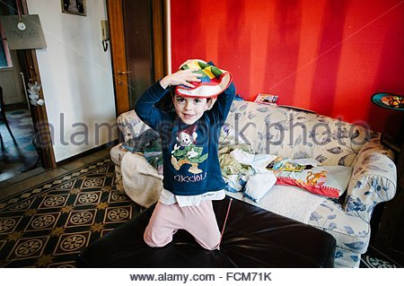 Child plays sitting on poof home - Stock Photo