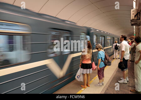 Passengers waiting to board a train arriving at the platform on the Metro in Saint Petersburg, Russia. - Stock Photo