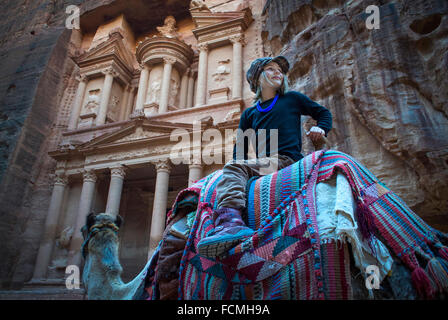 A young girl rides a Camel in front of the Treasury in Petra, Jordan. - Stock Photo