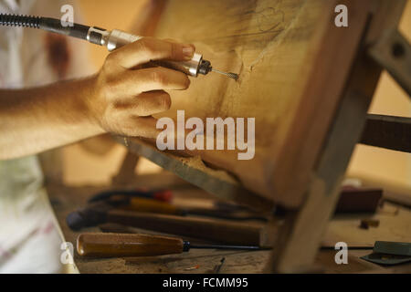 Adult man at work as artist, chiselling a bas-relief in his atelier. He works with a drill to chisel a wood painting. - Stock Photo