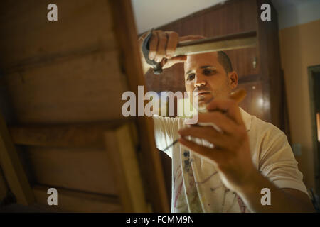 Adult man at work as artist, chiseling a bas-relief in his atelier. He works with hammer and chisel on a wood painting. - Stock Photo