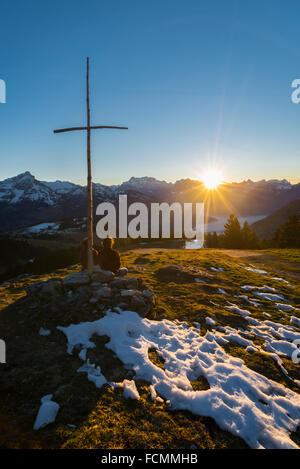 Couple watching a winter sunset over the snow covered Glarus mountains in the Swiss Apls from on viewpoint with - Stock Photo
