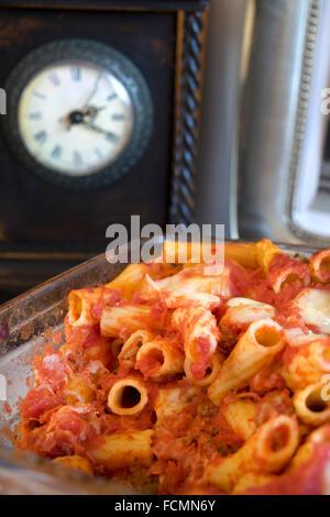 baked pasta with mozzarella salami eggs tomato sauce and cured ham - Stock Photo