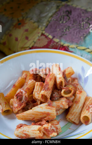 baked pasta with mozzarella salami eggs tomato sauce and cured ham - Stock Photo
