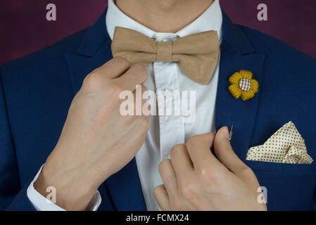 Man in blue suit with coffee cream bowtie color, flower brooch, and dot pattern handkerchief, close up, adjusting - Stock Photo