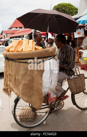 Man selling bread in front of the daily market on Darajani road, Stone Town, Unguja Island, Zanzibar Archipelago, - Stock Photo