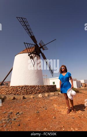 Woman posing in front of the windmill near Antigua, Fuerteventura, Canary Islands, Spain, Europe. - Stock Photo