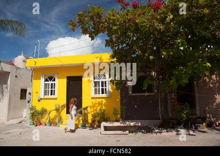 Woman in front of a yellow painted building in town center, Isla Mujeres, Cancun, Quintana Roo, Yucatan Province, - Stock Photo