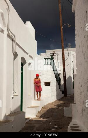 Woman posing in front of a whitewashed house in Faros village, Sifnos, Cyclades Islands, Greek Islands, Greece, - Stock Photo