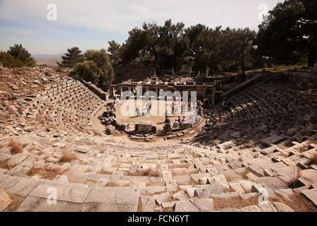 Tourists at the ancient amphitheater in the ruins of Priene, Aydin Province, Turkey, Europe. - Stock Photo