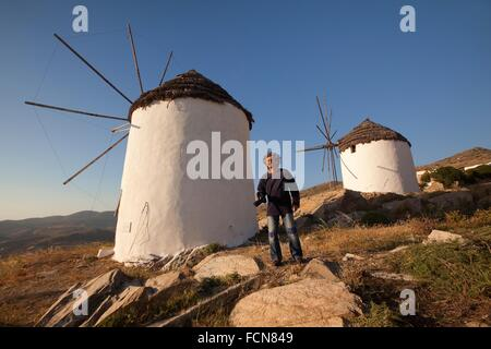 Tourist with a camera in front of old windmills in town center Chora, Ios, Cyclades Islands, Greek Islands, Greece, - Stock Photo